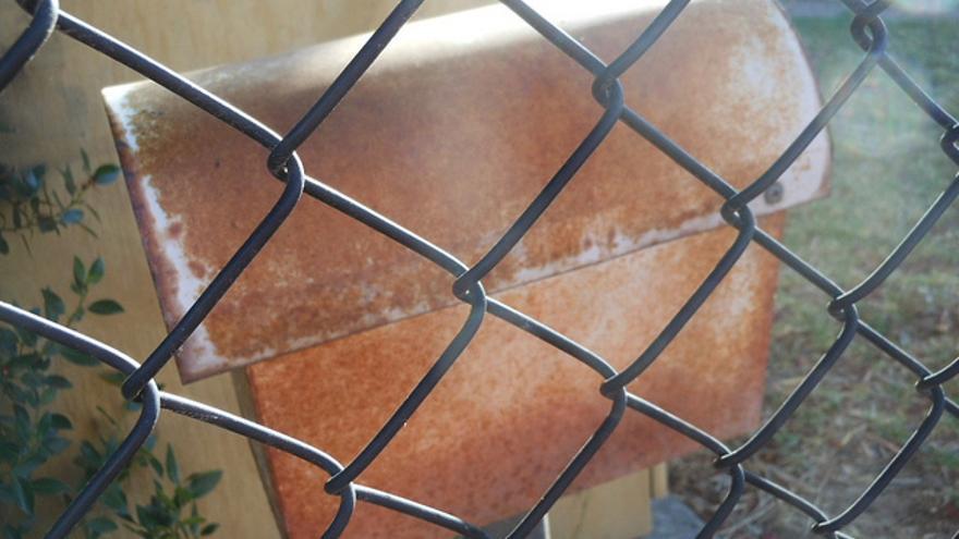 Un buzón tras una valla