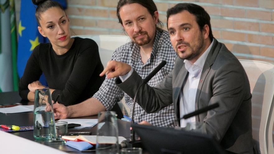 Pablo Iglesias escucha a Alberto Garzón durante el acto en la Facultad de Comunicación de Málaga.