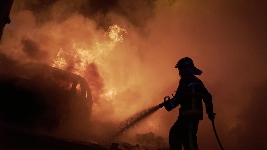 Un bombero apaga el fuego de las barricadas en el tercer día de protestas en Barcelona