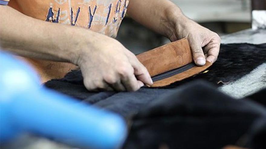 Trabajador remienda una prenda de vestir