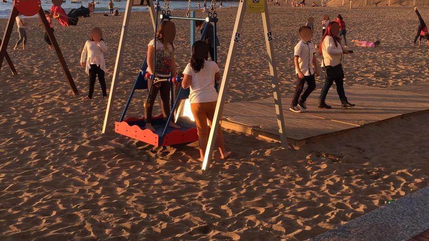 Columpio adaptado en la playa de Las Canteras siendo utilizado incorrectamente por una menor