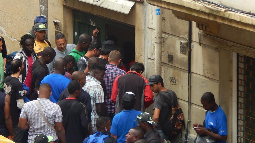 Migrantes subsaharianos se apelotonan frente al comedor social de Irala