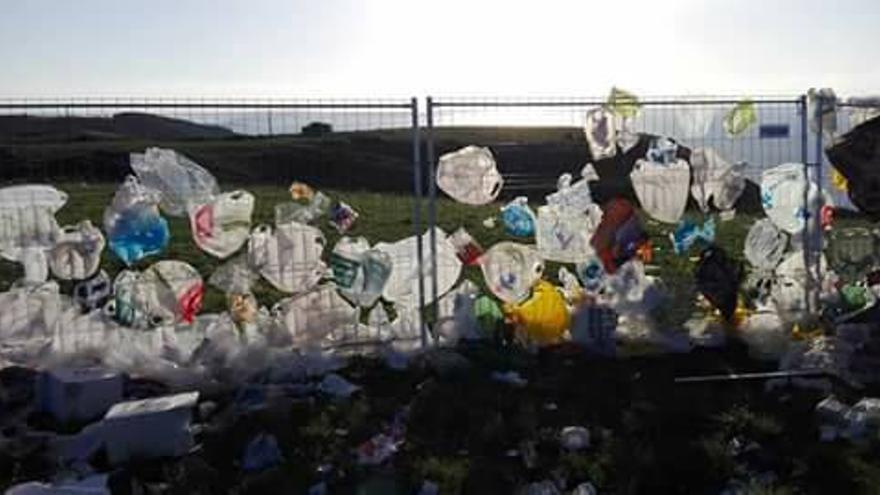 Las bolsas de basura pegadas a la valla debido al viento.