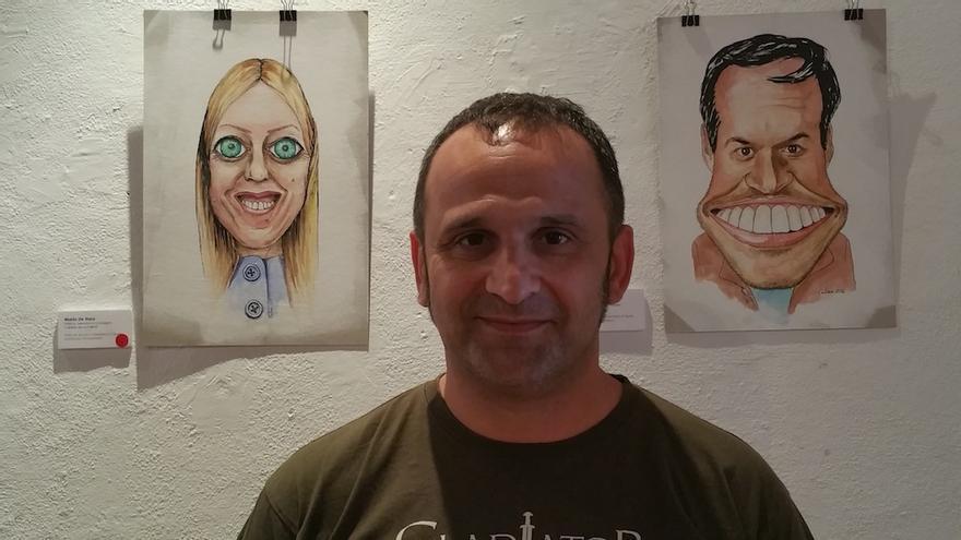 El ilustrador Carlos Manuel Rodríguez junto a caricaturas de María de Haro y Mariano Zapata. Foto: LUZ RODRÍGUEZ.
