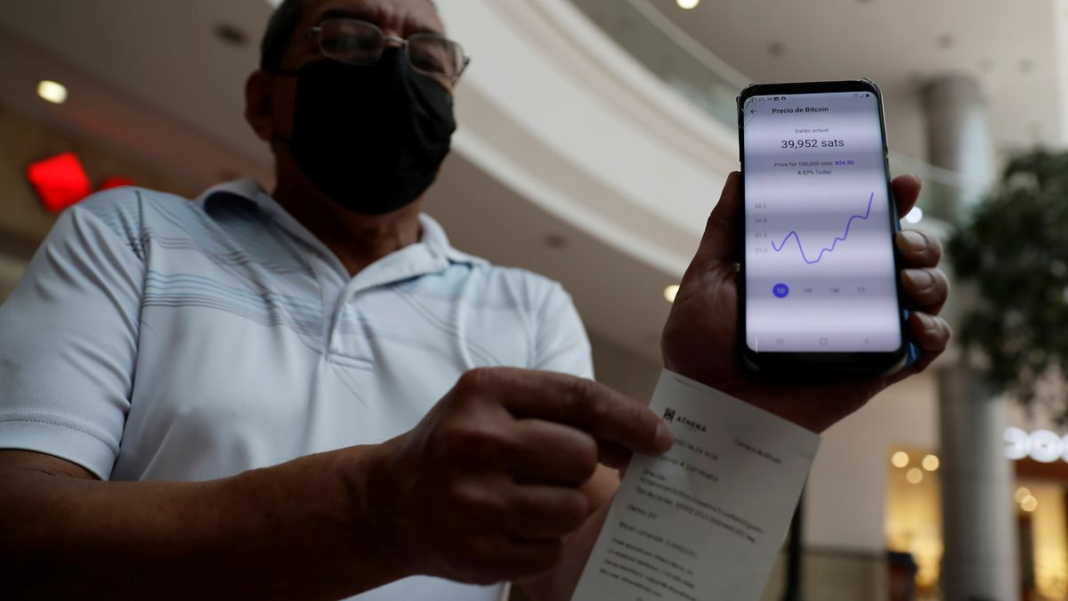 Un ciudadano salvadoreño muestra sus transacciones en bitcoin a través de su móvil, durante la inauguración de un nuevo cajero automático para transacciones con esta criptomoneda en un centro comercial en San Salvador (El Salvador).
