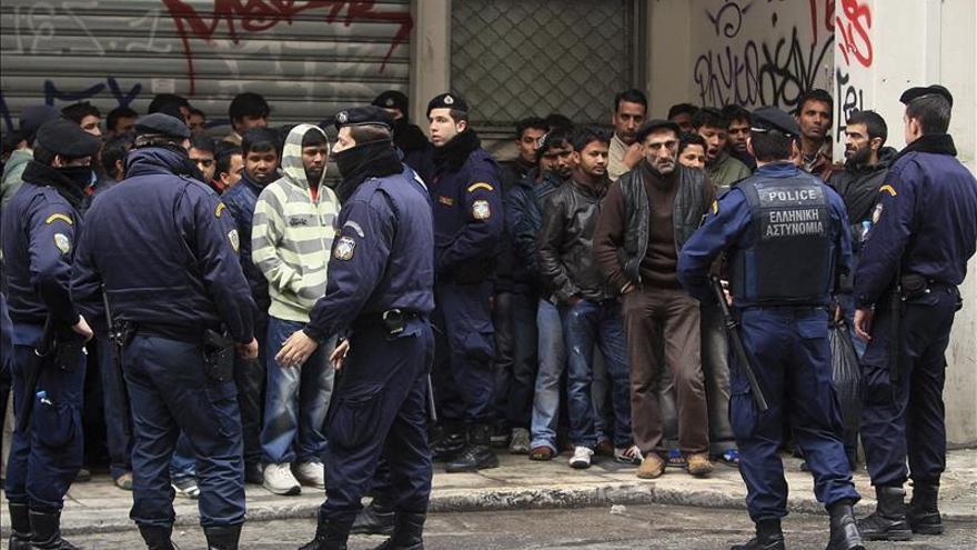 DAgentes de policías griegos vigilan a un grupo de inmigrantes durante una redada para comprobar sus identificaciones en Atenas, Grecia/ Efe
