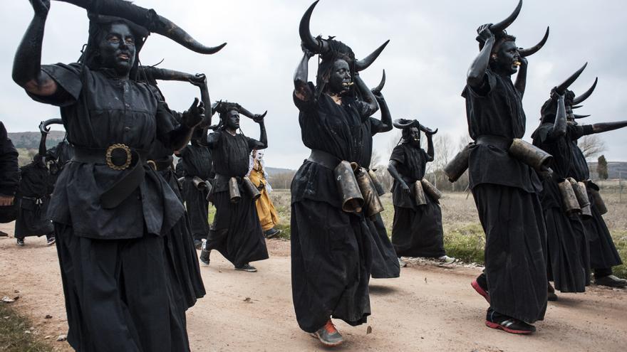 Los 'diablos' pintados de negro y agitando sus cencerros se dirigen al pueblo de Luzón (Guadalajara). Joaquín Gómez Sastre