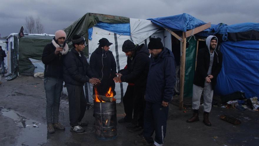 Varios migrantes y refugiados se calientan en una hoguera. Las condiciones de vida son muy duras en La Jungla, donde impera un tiempo lluvioso y frío, que empeora las condiciones del suelo, muy fangoso. | Mohammad Ghannam/MSF.