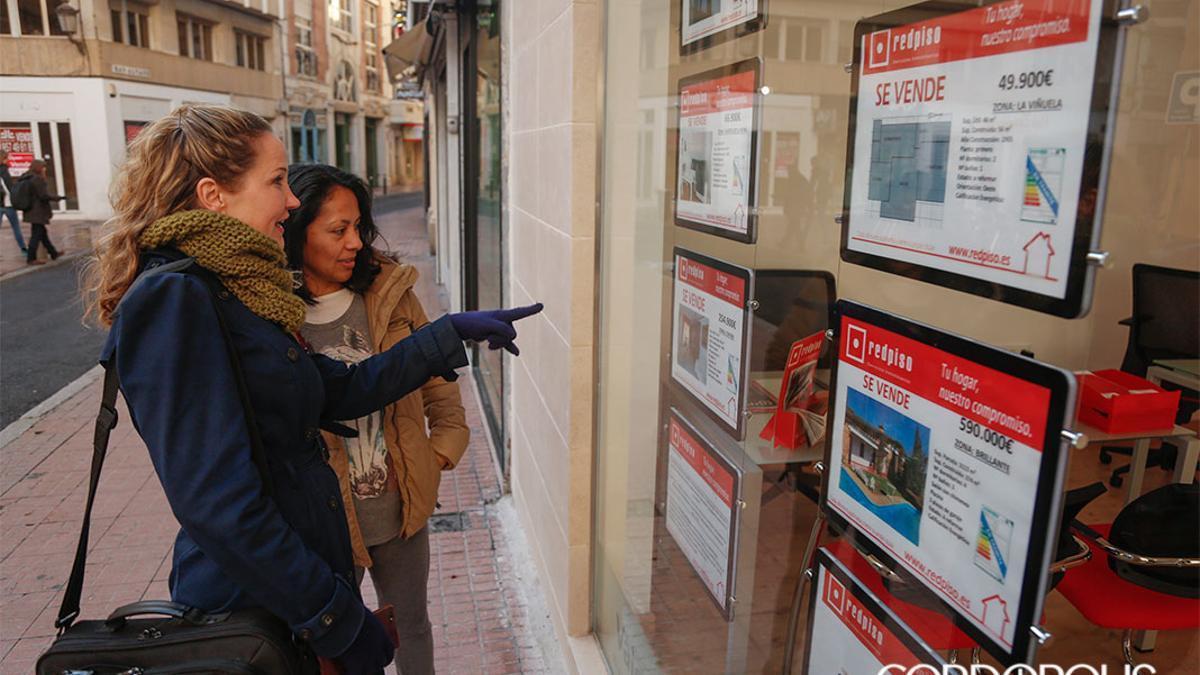 Dos mujeres observan los precios de una inmobiliaria
