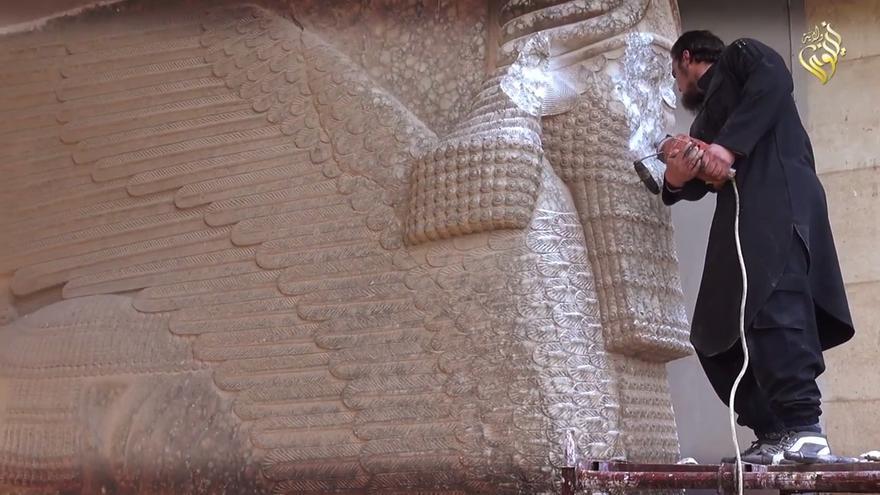 Un miembro del ISIS destruye la cara de una estatua en el museo de Nínive.