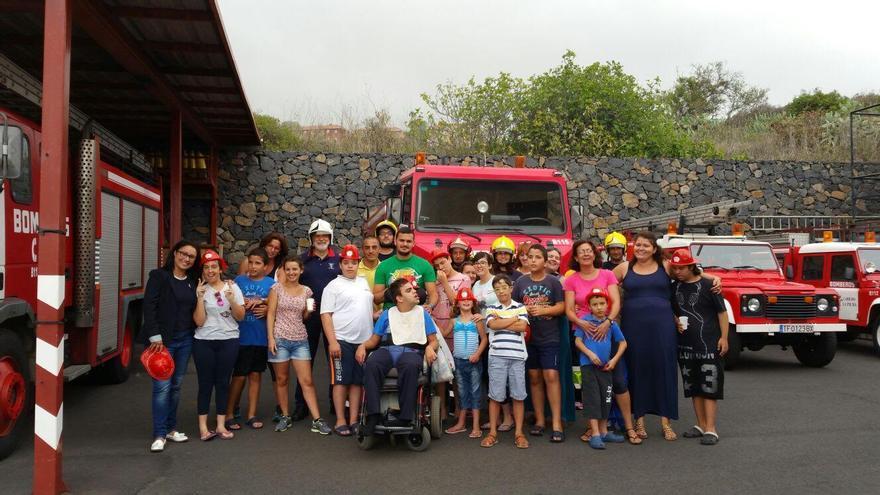 El grupo de jóvenes de Indispal y otros miembros de la plataforma posan con varios bomberos en el Parque  de La Grama.