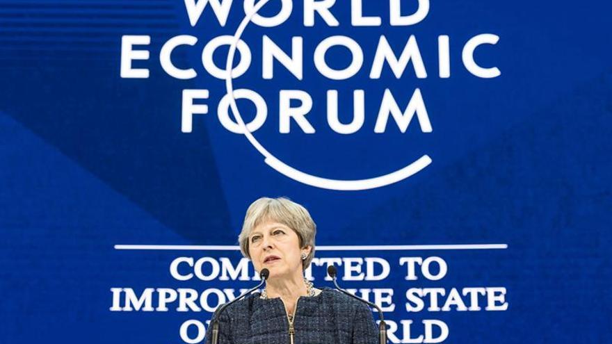 May defiende en Davos abrir barreras al libre comercio internacional