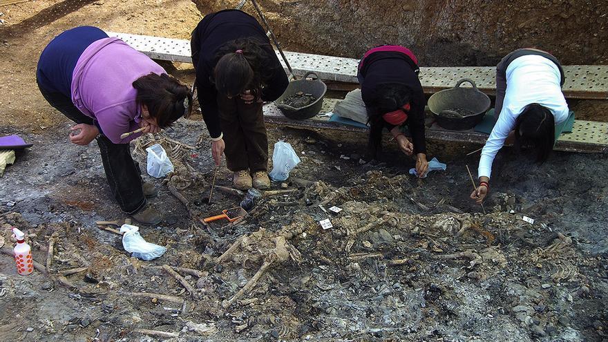 Equipo de arqueólogas trabajando en una fosa