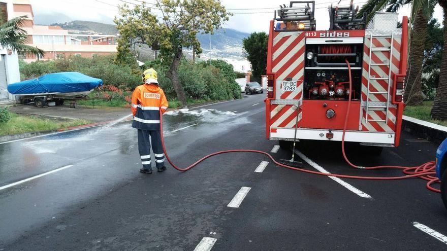 En la imagen, este domingo, los bomberos limpiando el derrame de combustible en la carretera LP-2, en la zona de El Cantillo-San Antonio, en Breña Baja. Foto: BOMBEROS LA PALMA.