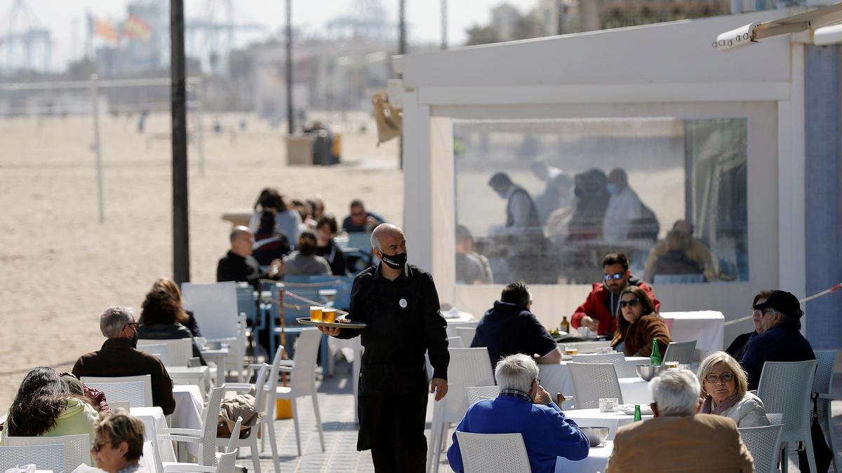 Un camarero atiende las mesas de una terraza en uno de los restaurantes de la playa de la Malvarrosa de Valéncia.