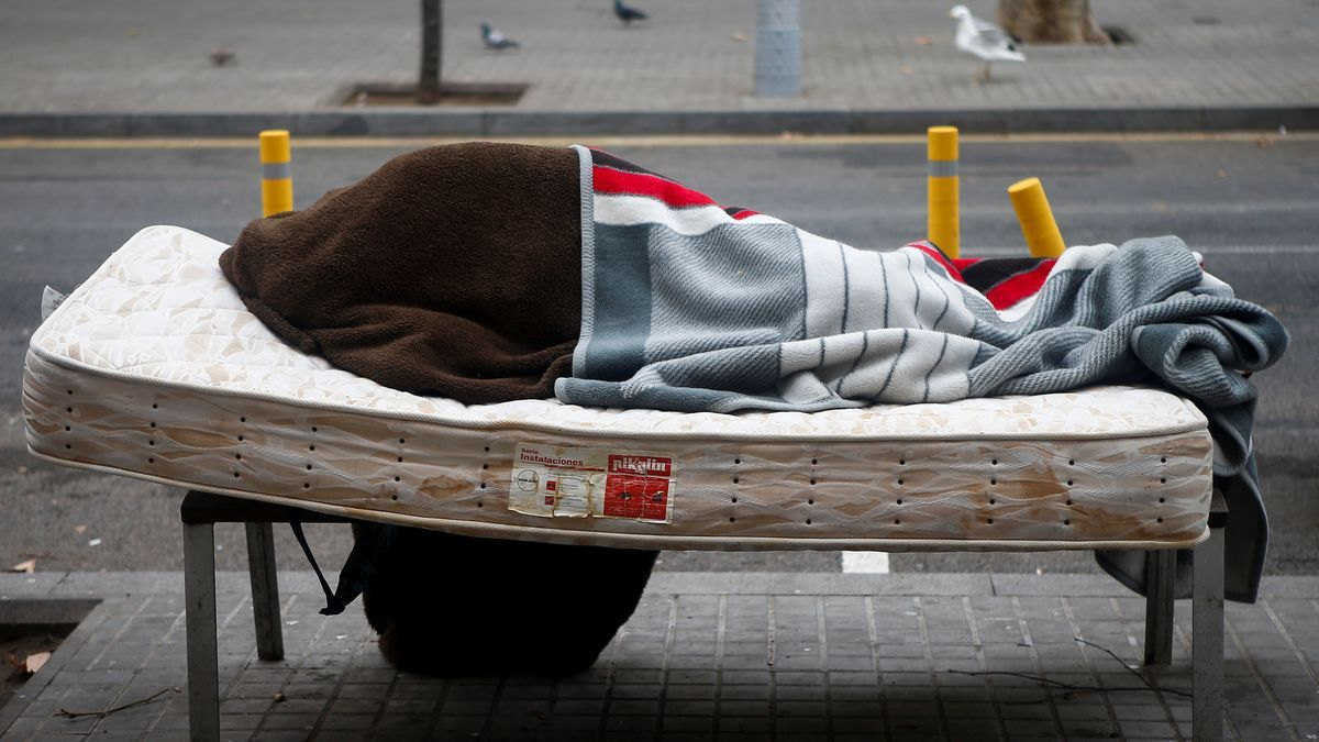 Imagen de archivo de una persona sin hogar descansando en un banco del barrio de Sant Andreu de Barcelona.