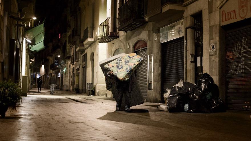 Un home amb dos matalassos a un carrer de Ciutat Vella, a Barcelona. / Edu Bayer