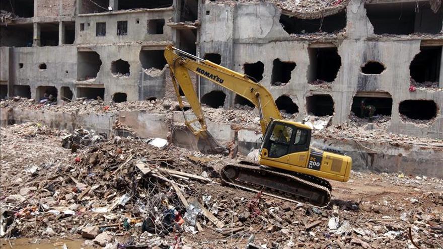 Una grua despeja el terreno en el edificio textil derrumbado en Bangladesh