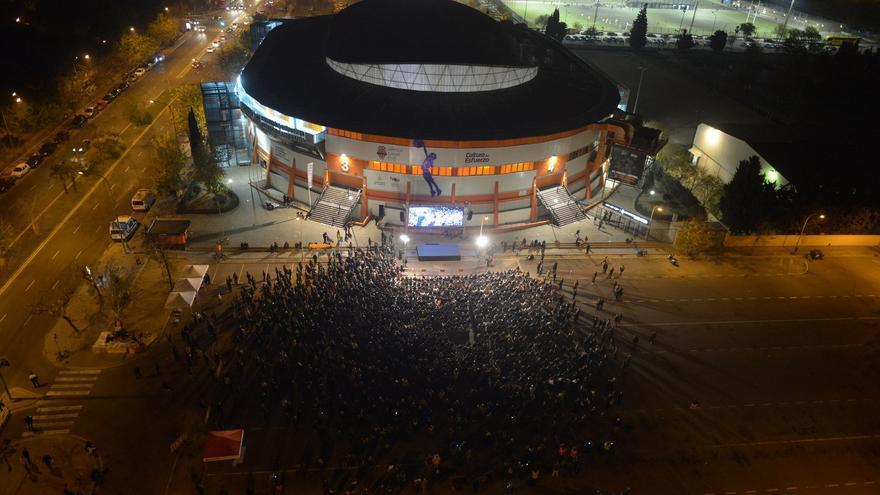Centenares de personas ven el mitin de Podemos en Valencia fuera del recinto a través de una pantalla.