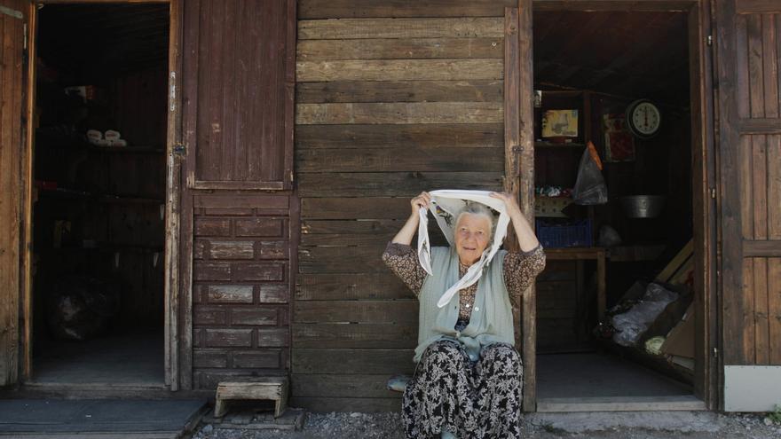 Naza Hasanovic, de 68 años, musulmana bosnia, se sienta frente a la pequeña tienda donde vende comida, en el centro colectivo para refugiados construido en 1995, cerca de la ciudad norteña bosnia de Zivinice, a 130 km al norte de Sarajevo, donde se instaló después de ser desplazada de su hogar en Srebrenica, en Bosnia oriental.