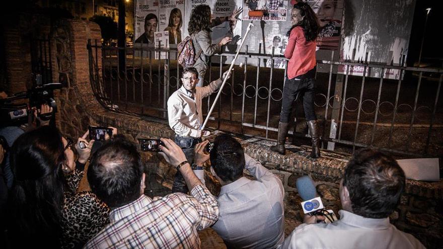 Luis Blanco, de Almendralejo en Común, durante la tradicional pegada de carteles rodeado por la prensa y compaleros de formación / MARIO CANO