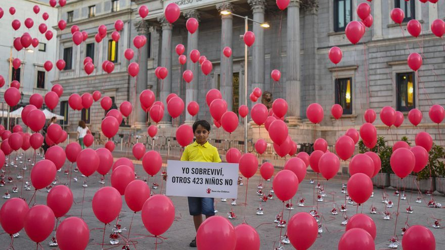 Said, de 8 años, frente al Congreso de los Diputados junto a 423 globos rojos que ha colocado la ONG Save The Children en recuerdo de los menores muertos en el Mediterráneo en el último año. | FOTO: Pedro Armestre/ Save The Children.