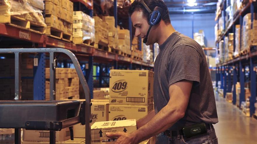 En la imagen, un trabajador usando la tecnología de voz en un centro de distribución.