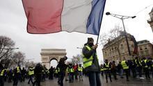 Un manifestante de los chalecos amarillos ondea una bandera francesa durante una protesta en París