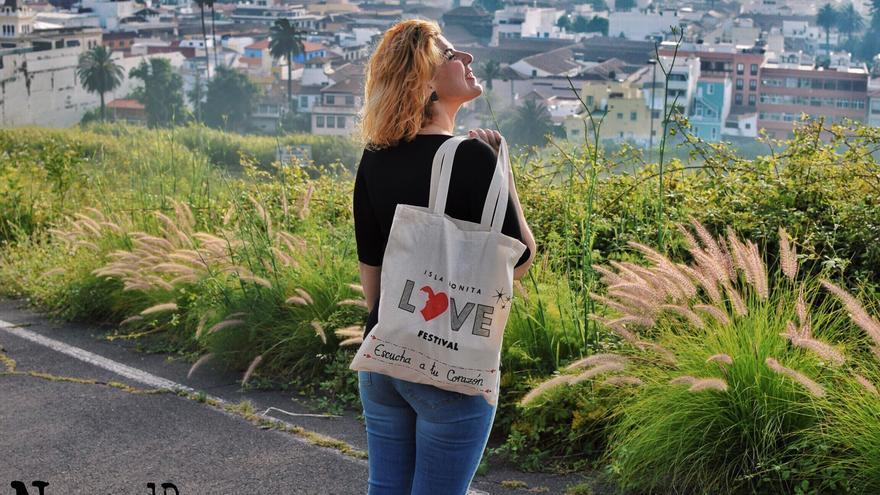 Naida muestra una de sus bolsas con el logo del Love Festival Isla Bonita.