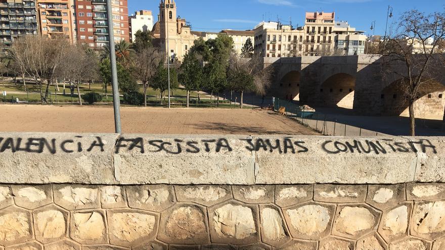 Una pintada fascista en el muro del antiguo cauce del río Túria, en Valencia