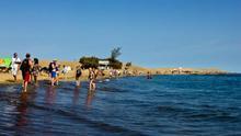 Turistas llegados al archipiélago en una playa con dunas, en Maspalomas (Gran Canaria)