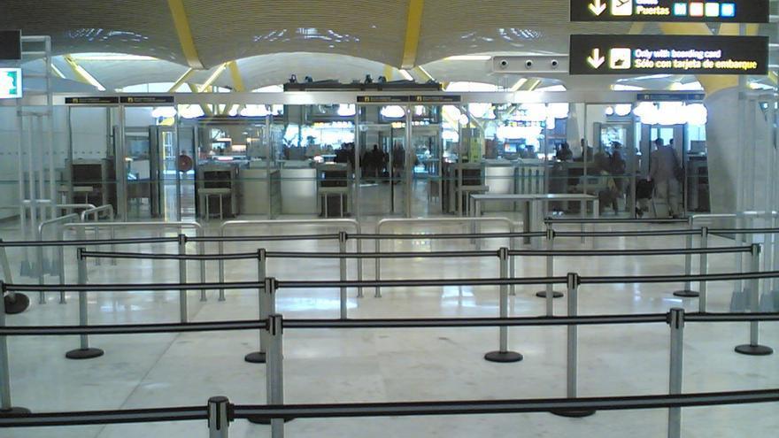 Un puesto de control vacío en un aeropuerto, con las cintas que delimitan el espacio para guardar la cola en caso de multitud