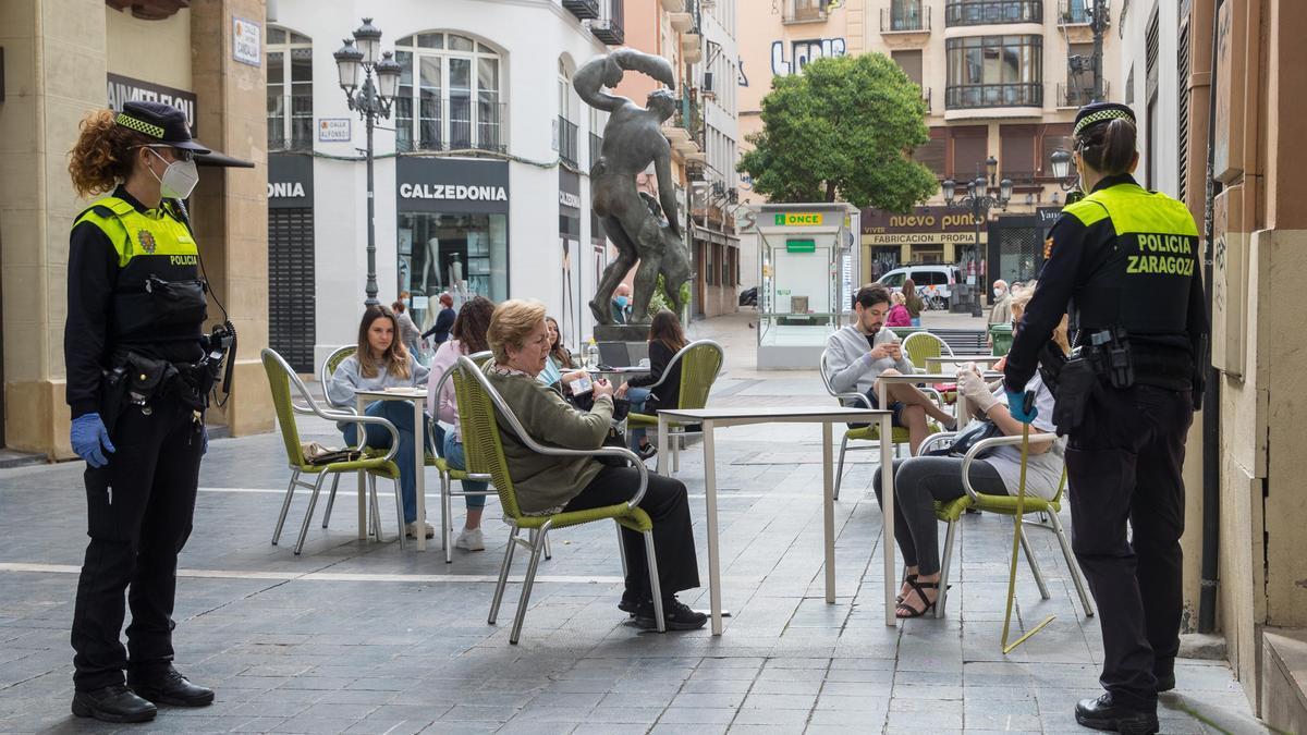 Una patrulla de la Policía Local mide las distancias de las mesas de una terraza en el casco viejo de Zaragoza. EFE/Javier Cebollada/Archivo