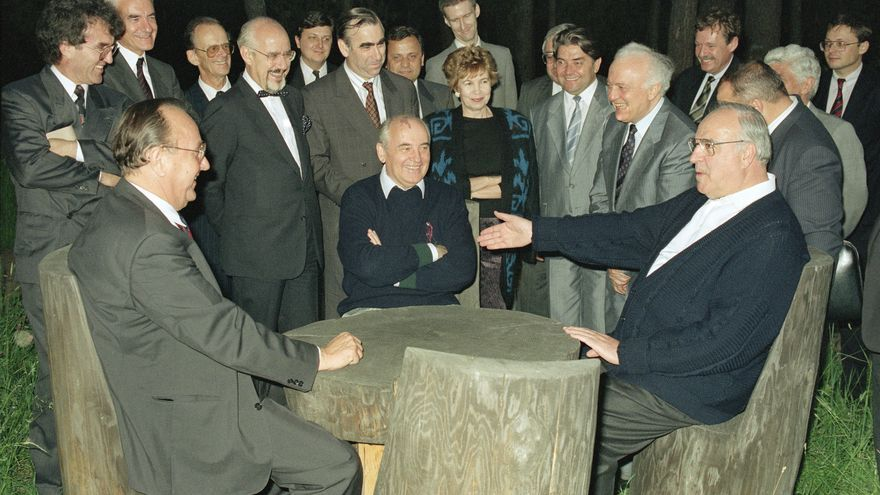 Soviet President Mikhail Gorbachev, seated at center, is shown with West German Chancellor Helmut Kohl, right, and Foreign Minister Hans-Dietrich Genscher, July 17, 1990, at a table in the garden of the guest house in Archiz during a break in their talks about the NATO membership of United Germany, one of the most difficult remaining hurdles to German reunification. In the background, left to right: Hans Klein (4th from left); West German Finance Minister Theo Waigel (6th from left); Raisa Gorbachev; Soviet Finance Minister Valentin Pavlov; and Soviet Foreign Minister Eduard Schevardnadze. Others are unidentified.
