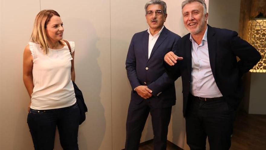 El secretario general del PSOE de Canarias, Angel Víctor Torres (d) y los diputados electos de Podemos Noemí Santana (i) y Nueva Canarias Román Rodríguez (c), conversan en medio de las reuniones que el primero ha mantenido con ambos en la ronda de negociaciones