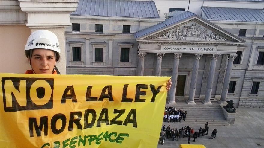 Activista de Greenpeace antes de descolgar una pancarta en octubre de 2014. / Gpeace