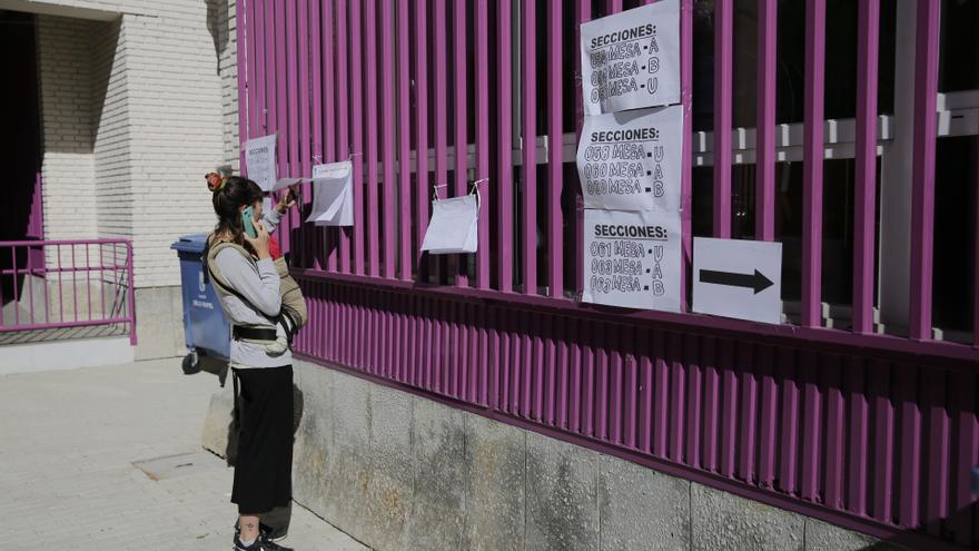 Una mujer con su hijo comprueba dónde le toca votar