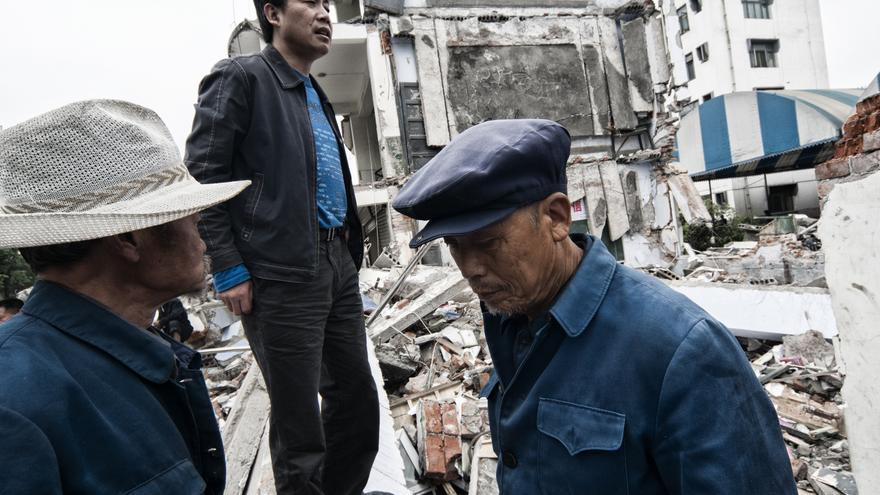 Varios hombres buscan entre los restos del edificio en el que vivían enseres que todavía sean de valor. Entre los tres de la fotografía perdieron a cinco familiares en Dujiangyan./ Zigor Aldama.