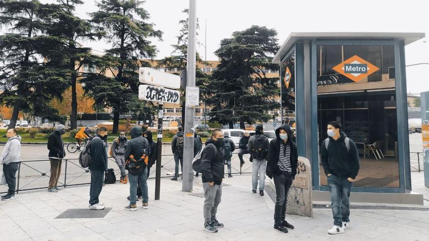 Decenas de personas esperan en la plaza Elíptica (Carabanchel) por trabajos sin contrato ni derechos laborales.