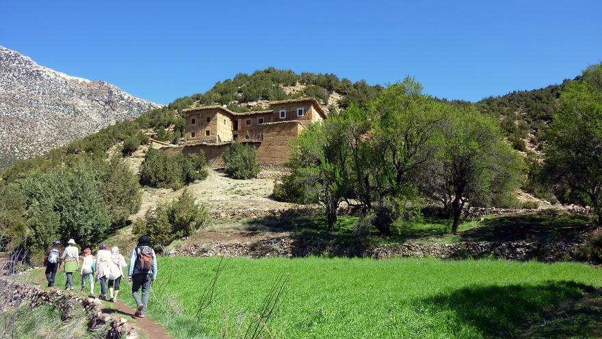 Senderistas pasan junto a los cultivos de una aldea bereber en el Valle de los Ait Bouguemez, uno de los más remotos del Atlas marroquí. Pascal Blachier
