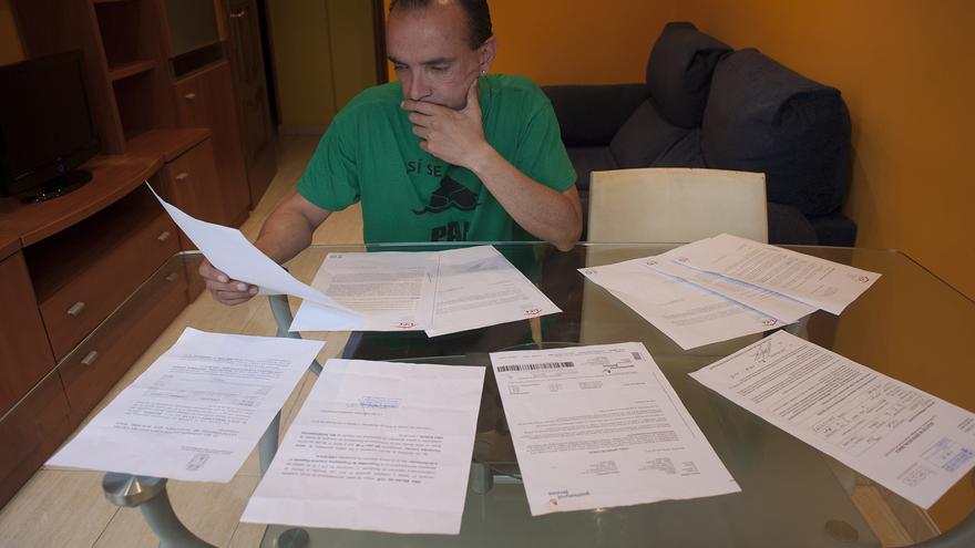 Jesús observa la documentación que le garantiza la dación en pago de su casa. | JAVO DÍAZ