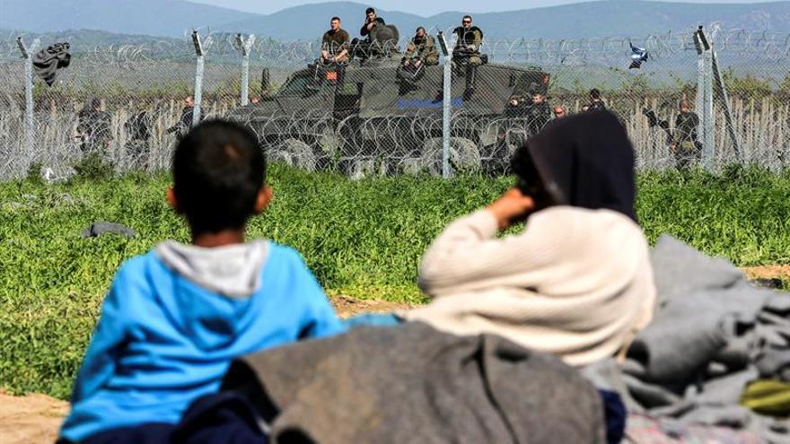 Unos niños descansaban el martes junto a la valla fronteriza del campamento de refugiados de Idomeni, en Grecia, mientras la policía vigila la frontera. | Efe