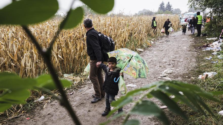 Un niño de Siria y su padre caminan hacia el lado croata de la frontera de Bapska. / Foto: Achilleas Zavallis