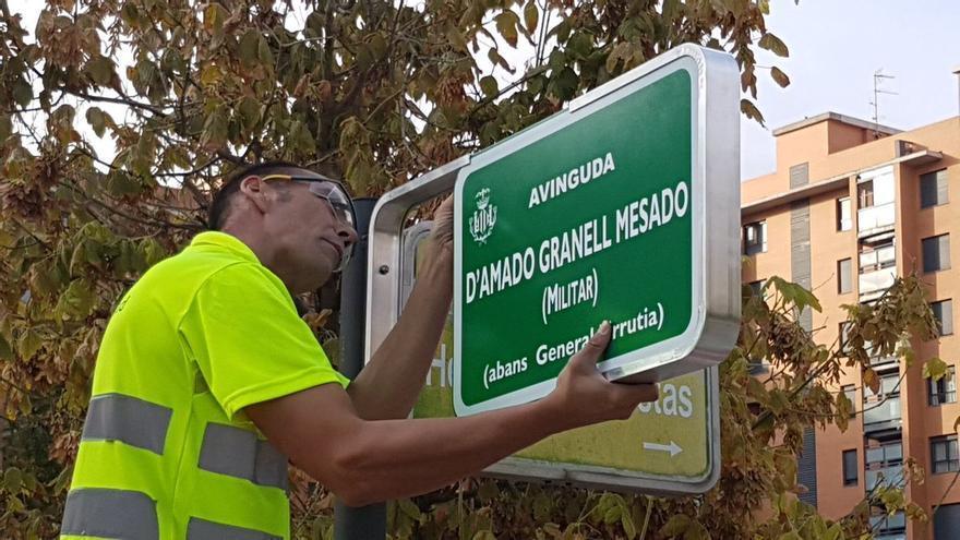 Un operario coloca la placa de la avenida Amado Granell en el vial que antes se denominaba General Urrutia en Valencia