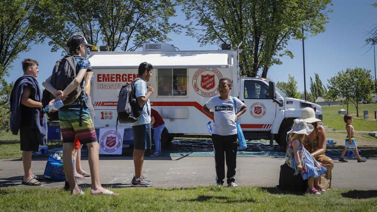 Canadienses frente a un camión de emergencias en plena ola de calor.