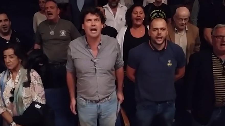 Un grupo de asistentes al pleno de Latina cantando el himno de la Legión