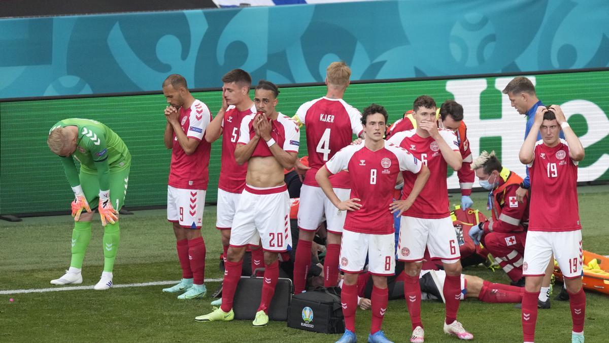 El danés Eriksen es tapado por sus compañeros después de desplomarse en pleno partido