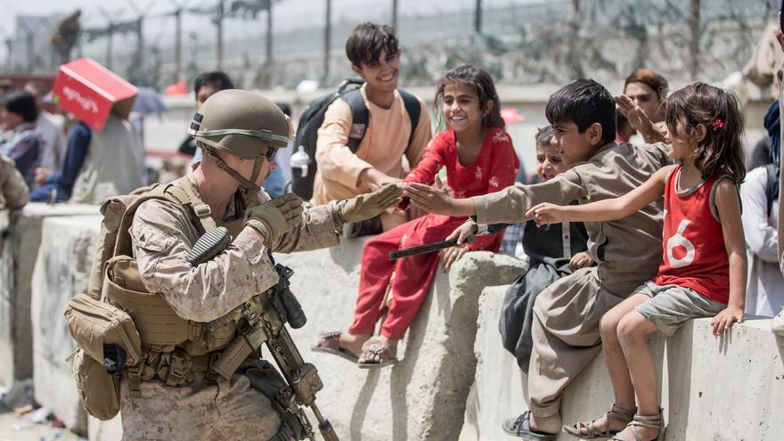Un grupo de niños juega con un marine de EEUU durante la evacuación en el aeropuerto de Kabul.