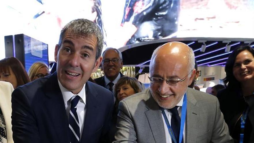 El presidente del Gobierno de Canarias, Fernando Clavijo (i), y el presidente del Cabildo de Gran Canaria, Antonio Morales, señalan la costa de Maspalomas en un mapa de la isla de Gran Canaria en la World Travel Market de Londres