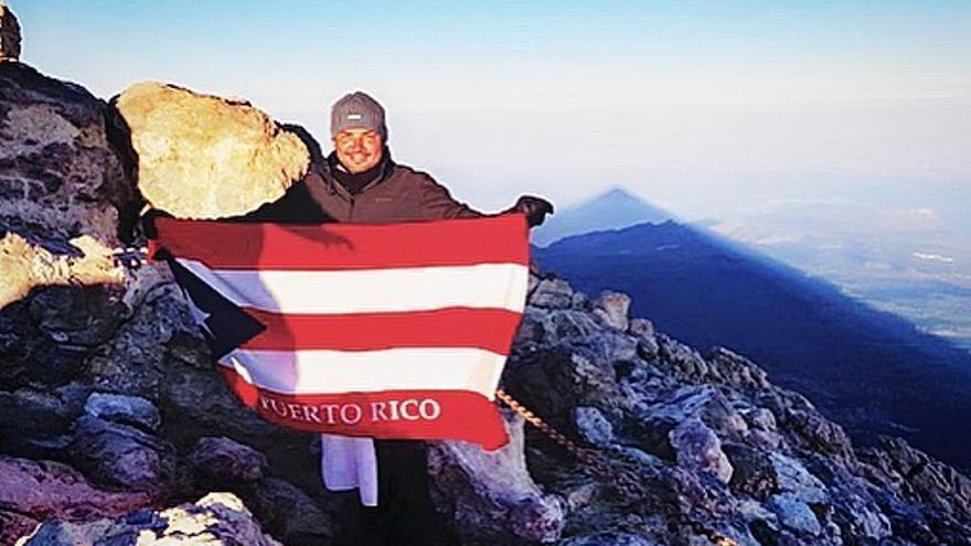 Manny Manuel, en la cumbre del volcán Teide, en Tenerife, con la bandera de su país